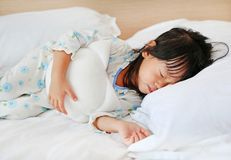 Adorable little girl sleeping in the bed with her toy.  Stock Photo