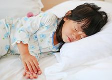 Adorable little girl sleeping in the bed with her toy.  Royalty Free Stock Image