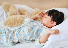 Adorable little girl sleeping in the bed with her toy.  Stock Photos