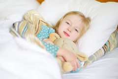 Adorable little girl sleeping in the bed with her toy Royalty Free Stock Photos