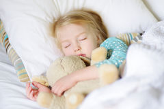 Adorable little girl sleeping in the bed with her toy Stock Photo