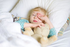 Adorable little girl sleeping in the bed with her toy Stock Images
