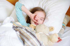 Adorable little girl sleeping in the bed with her toy Royalty Free Stock Photo