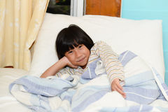 Adorable little girl sleeping in a bed. Look at camera Stock Images