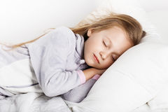 Adorable little girl sleeping in the bed. In warm pajamas against white background Stock Photo