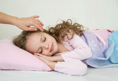 Adorable little girl sleeping in her bed. Mother's hand touching girl's head.  Nighty night! good night Stock Images