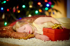 Adorable little girl sleeping under the Christmas tree by a fireplace. On Christmas eve Royalty Free Stock Photos