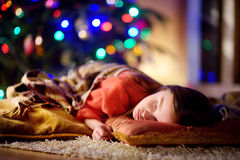 Adorable little girl sleeping under the Christmas tree by a fireplace Royalty Free Stock Images
