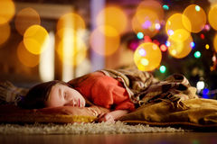 Adorable little girl sleeping under the Christmas tree by a fireplace. On Christmas eve Royalty Free Stock Photo