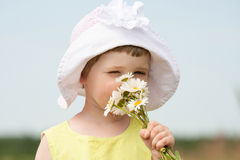 Adorable little girl smelling summer flowers Royalty Free Stock Image