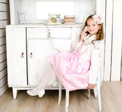 Adorable little girl sreaking by phone in vintage interior Stock Photo