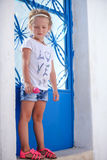 Adorable little girl standing near blue door of Stock Images