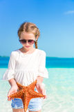 Adorable little girl with starfish on white empty beach Royalty Free Stock Photos