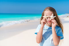 Adorable little girl with starfish on white empty beach Royalty Free Stock Photography