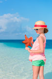 Adorable little girl with starfish on white empty beach Stock Photos