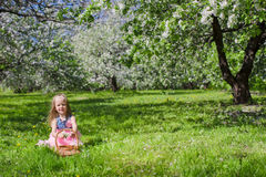 Adorable little girl with straw basket in. Little adorable girls with butterfly wings under blossoming apple tree Stock Image