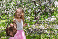 Adorable little girl with straw basket in. Little adorable girls with butterfly wings under blossoming apple tree Stock Photos