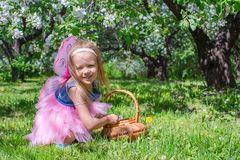 Adorable little girl with straw basket in. Little adorable girls with butterfly wings under blossoming apple tree Royalty Free Stock Photo
