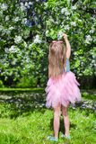 Adorable little girl with straw basket in. Little adorable girls with butterfly wings under blossoming apple tree Stock Images