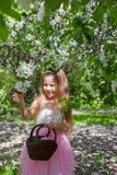 Adorable little girl with straw basket in. Little adorable girls with butterfly wings under blossoming apple tree Stock Photo
