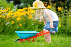 Adorable little girl in straw hat having fun with a toy wheelbarrow. Cute child playing farm outdoors. royalty free stock photography