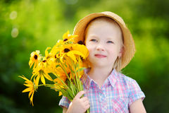 Adorable little girl in straw hat holding beautiful yellow flowers Stock Photo