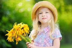 Adorable little girl in straw hat holding beautiful yellow flowers Royalty Free Stock Image