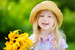 Adorable little girl in straw hat holding beautiful yellow flowers Stock Photos