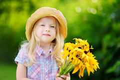 Adorable little girl in straw hat holding beautiful yellow flowers for her mother Stock Image