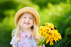 Adorable little girl in straw hat holding beautiful yellow flowers for her mother Royalty Free Stock Photography