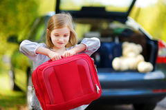 Adorable little girl with a suitcase. Leaving for a car vacation with her parents Stock Photos