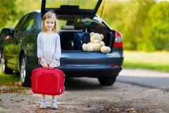 Adorable little girl with a suitcase. Leaving for a car vacation with her parents Royalty Free Stock Images