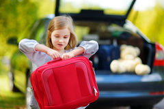 Adorable little girl with a suitcase. Leaving for a car vacation with her parents Stock Image