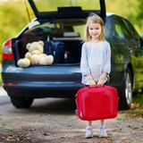 Adorable little girl with a suitcase. Leaving for a car vacation with her parents Royalty Free Stock Photo