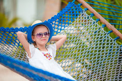 Adorable little girl on summer vacation relaxing in hammock Stock Photo