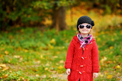 Adorable little girl in sunglasses on autumn day Stock Images