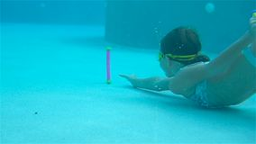 Adorable little girl in the swimming pool underwater. The little girl in the water park swimming underwater and smiling stock video