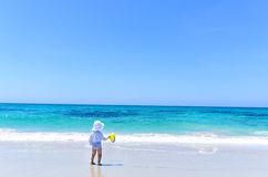 Adorable little girl in swimsuit having fun at tropical sandy beach Stock Images