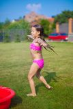 Adorable little girl in a swimsuit playing and Stock Image