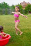 Adorable little girl in a swimsuit playing and Stock Photography