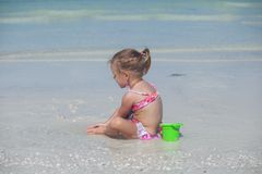 Adorable little girl in swimsuit playing at Royalty Free Stock Image