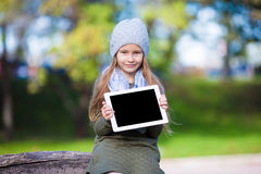 Adorable little girl with tablet PC outdoors in Royalty Free Stock Photo