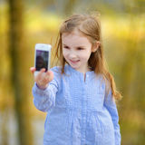 Adorable little girl taking a photo of herself Royalty Free Stock Image
