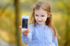 Adorable little girl taking a photo of herself Royalty Free Stock Photos