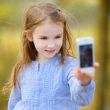 Adorable little girl taking a photo of herself Stock Photo