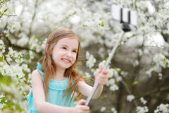 Adorable little girl taking a photo of herself with a selfie stick Royalty Free Stock Photo