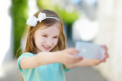 Adorable little girl taking a photo of herself Stock Images