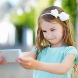Adorable little girl taking a photo of herself Royalty Free Stock Photo