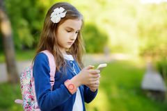 Adorable little girl taking a photo with a smartphone on beautiful summer day. Kids using mobile devices Stock Image