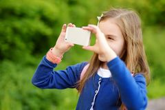 Adorable little girl taking a photo with a smartphone on beautiful summer day. Kids using mobile devices Royalty Free Stock Photos